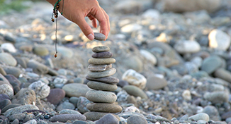 Image of A person stacking pebbles